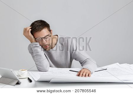 Tired Young Attractive Man Sleeps At Work Place, Has Much Work, Being Fatigue And Exhausted, Isolate
