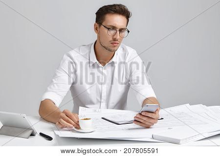 Focused male office worker uses smart phone for online communication drinks espresso or cappuccino sits at work place has serious expression. Young man works on architectual project alone stock photo