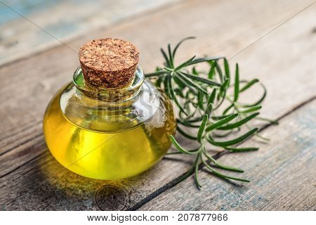 Rosemary essential oil in a glass bottle with cork stopper and fresh rosemary herb on wooden background stock photo