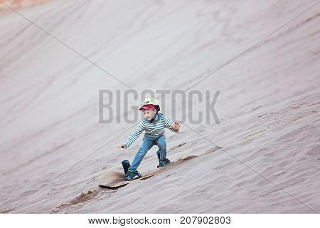 brave little boy sandboarding in valle de la muerte in atacama desert chile active healthy lifestyle concept