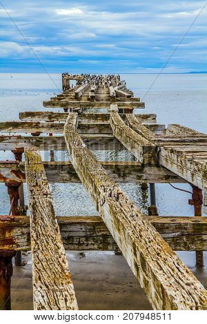 Rusted and destroyed remains of the sea mooring. South of South America. The legendary Strait of Magellan. Cloudy autumn morning. The concept of extreme and active tourism stock photo
