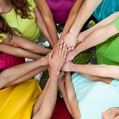 High perspective of group of companions demonstrating solidarity with their hands together