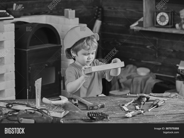Child In Helmet Cute Playing As Builder Or Repairer, Repairing Or Handcrafting. Handcrafting Concept