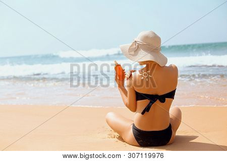 Sun cream on tanned shoulder with sun shape . Sun protection. Beautiful woman in bikini applying  Solar Cream. Skin and body care.Portrait of female holding suntan lotion and moisturizing sunblock. stock photo