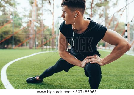 Outdoors image of muscular young man streching out against nature background. Athlete man looking away, stretching his leg and listening the music on earphones. Sport, lifestyle and people concept. stock photo
