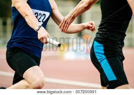 relay race men athletes runners passing baton competition in athletics stock photo