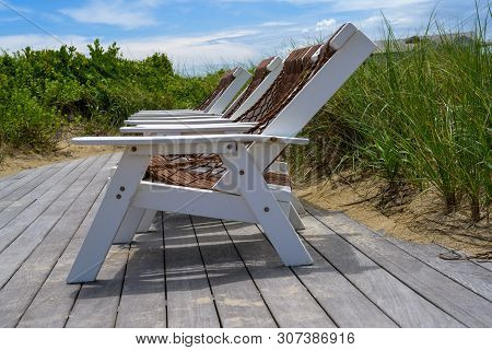 Photo of a row of beach chairs perched on a wooden platform on a sand dune in Duck, North Carolina, in the Outer Banks. stock photo