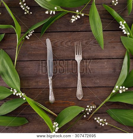 Plate and decor of lily of the valley flowers on the background of vintage wooden boards. Vintage background with flowers and place under the text. View from above. Flat lay. Cutlery. Vintage. stock photo