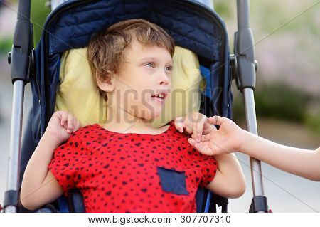 Communication of boy and a disabled girl in a wheelchair walking in the Park summer. Inclusion. Child cerebral palsy. Family with disabled kid. stock photo