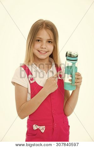 Stay hydrated. Girl cares about health and water balance. Girl on smiling face posing with water bottle isolated white background. Kid girl with long hair pointing at bottle. Water balance concept. stock photo