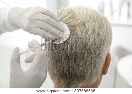 Senior man with hair loss problem receiving injection in salon stock photo