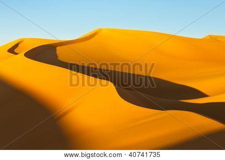 Sahara desert sunset. Shadows grow in the sand sea. stock photo