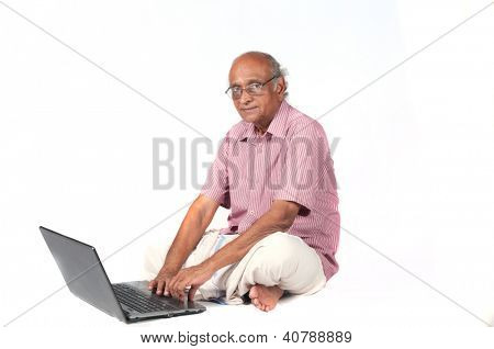 an old Indian man surfing the net after retirement stock photo