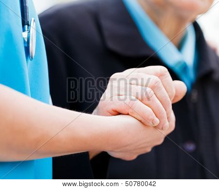 Caring nurse or doctor holding elderly lady's hand with care. stock photo
