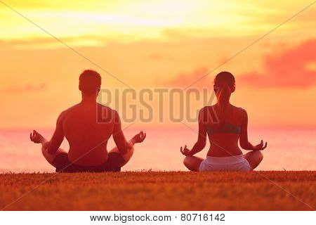 Meditation yoga couple meditating at serene beach sunset. Girl and man relaxing in lotus pose in cal