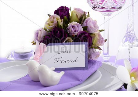 Purple theme wedding table place setting with heart shape plates and vintage silverware. stock photo