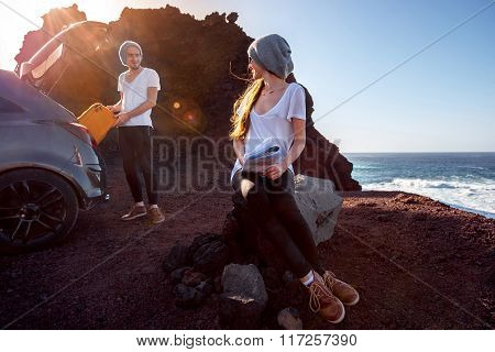 Young and pretty couple dressed alike enjoying their travel near the car with map and suitcase on the rocky coast on the sunset stock photo