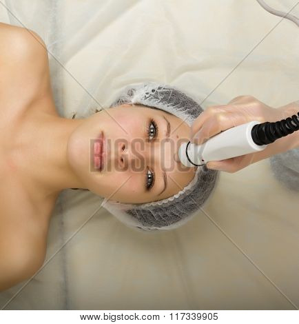 Beautician examining the face of a young female client at spa salon. getting rf-lifting in a beauty salon. Professional consultation. stock photo