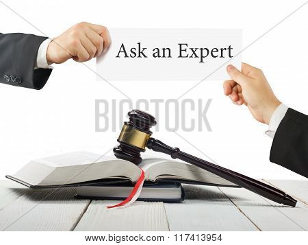 Law book and wooden judges gavel on table in a courtroom or law enforcement office. Lawyer Hands holding business card with text Ask an Expert. stock photo