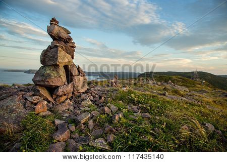 Located in St. John's Newfoundland and Labrador Signal Hill is a popular tourist attraction. Locals often build inuksuits out of the rocks and stones on the many trails. In the background is Cabot Tower and Cape Spear in the distance. stock photo