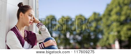 people, emotion and teens concept - sad unhappy pretty teenage girl sitting on windowsill over summe