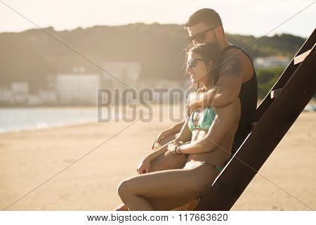 Romantic couple in hug watching sunrise/ sunset together.Young man and woman in love hugging and enjoying day at the beach.Flirting on summer vacation.Watching horizon,waves.Romance.Young love.Date stock photo