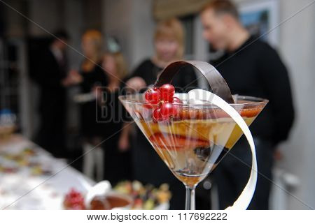 Fruit cocktail. Mix of red currant berries biscuit orange juice white and dark chocolate. Tapered wine glass. Unidentifiable People in blur at a table in the background. stock photo