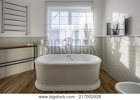 White bath with a chrome shower in the modern bathroom with light walls with tiles. There is a window with curtain, wooden rack with towels, heated towel rail, TV on the wall, toilet. Horizontal. stock photo