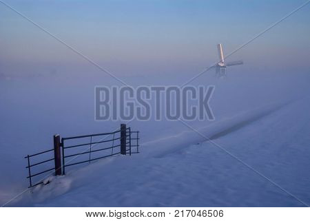 Windmill in a misty and wintry landscape near Oud-Alblas in the Dutch region Alblasserwaard stock photo