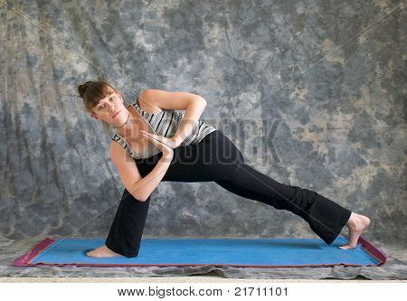Young woman on yoga mat Yoga posture Parivrtta Parsvakonasana or Revolved Extended Side Angle pose with hands in prayer position against a grey background facing left lit by diffused sunlight. stock photo