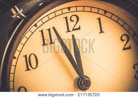 old grunge vintage alarm clock is showing midday or midnight movement. It is twelve o'clock holiday happy new year festive and christmas or lunch concept stock photo