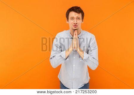 Please help! Man crying and apologize. Studio shot orange background stock photo
