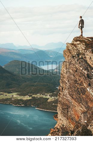 Man standing on cliff mountains over fjord Norway landscape Travel Lifestyle success motivation concept adventure active vacations outdoor stock photo