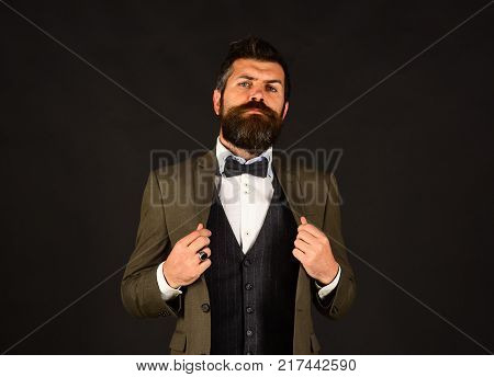 Man in retro suit and vest on brown background. Director or entrepreneur with stylish beard and moustache. Businessman with throughtful face holds arms crossed. Entrepreneurship and business concept stock photo