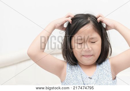 kid with freckles scratching his hair for head lice or allergies Health care concept stock photo