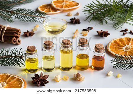 Christmas selection of essential oils and spices on white background: bottles of essential oil spruce fir frankincense resin star anise cinnamon clove dried orange. stock photo