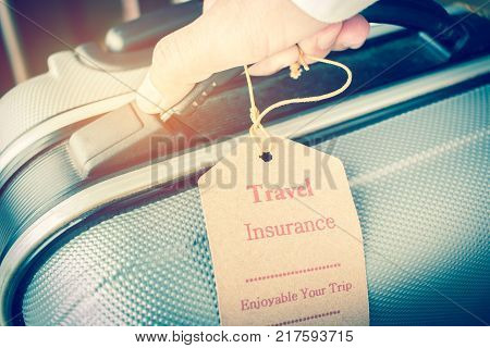 Hands holding Travel Insurance tag on Suitcase safety with letters enjoyable your trip on bag light blurred background that is intended cover medical expenses trip cancellation or flight accident. stock photo