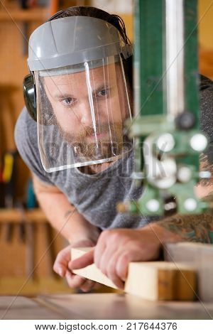 Carpenter using band saw for cutting wood in a workshop for woodwork. Man with tattoo and beard using safety mask with visor. stock photo