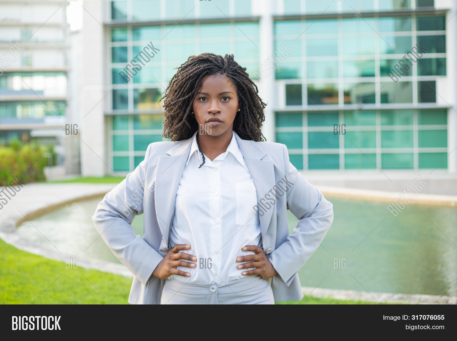 adult,akimbo,black,building,business,businesswoman,camera,career,ceo,city,company,concept,corporate,determined,dread,employee,entrepreneur,executive,female,hand,hip,job,leader,leadership,lifestyle,looking,manager,office,out,outdoors,outside,pensive,people,portrait,posing,professional,serious,standing,success,suit,thinking,urban,woman,work,young