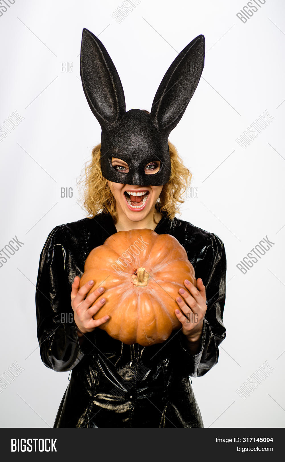 Happy woman in bunny mask with jack o lantern. Woman in bunny mask with pumpkin. Halloween costume. 31 October. Adorable blonde girl in black halloween bunny costume. Sexy girl in Halloween party.