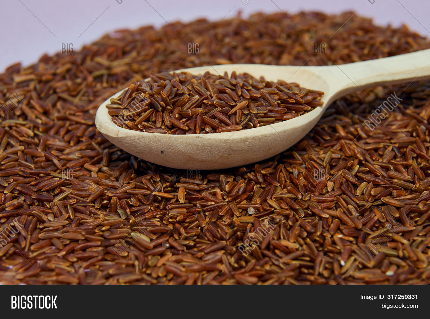 Unpolished Red Rice In Wooden Spoon. Long Grain Red Rice. Rice Background. Red Rice. Row Rice.