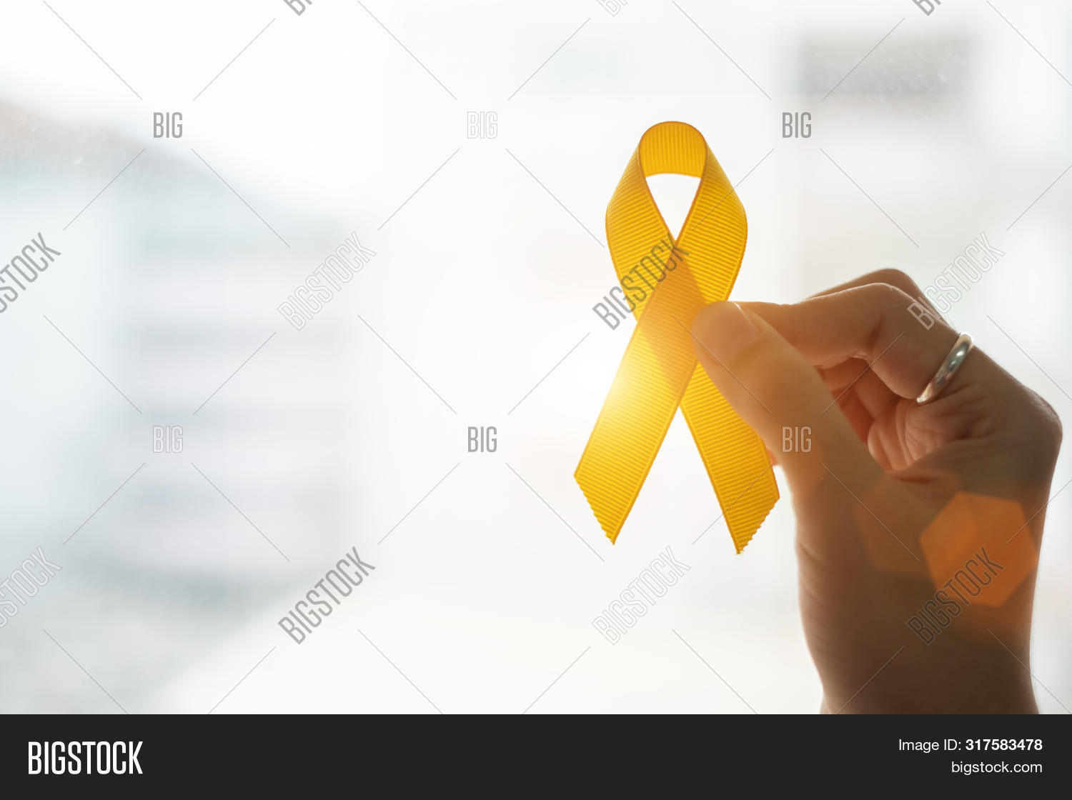 Suicide Prevention And Childhood Cancer Awareness, Yellow Ribbon On Wooden Background  For Supportin
