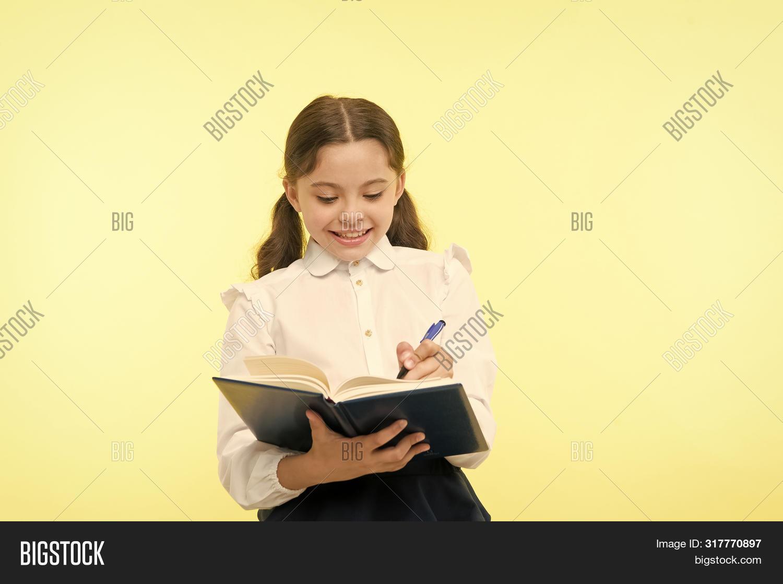 Making Notes. Child School Uniform Kid Doing Homework. Child Girl School Uniform Clothes Hold Book A