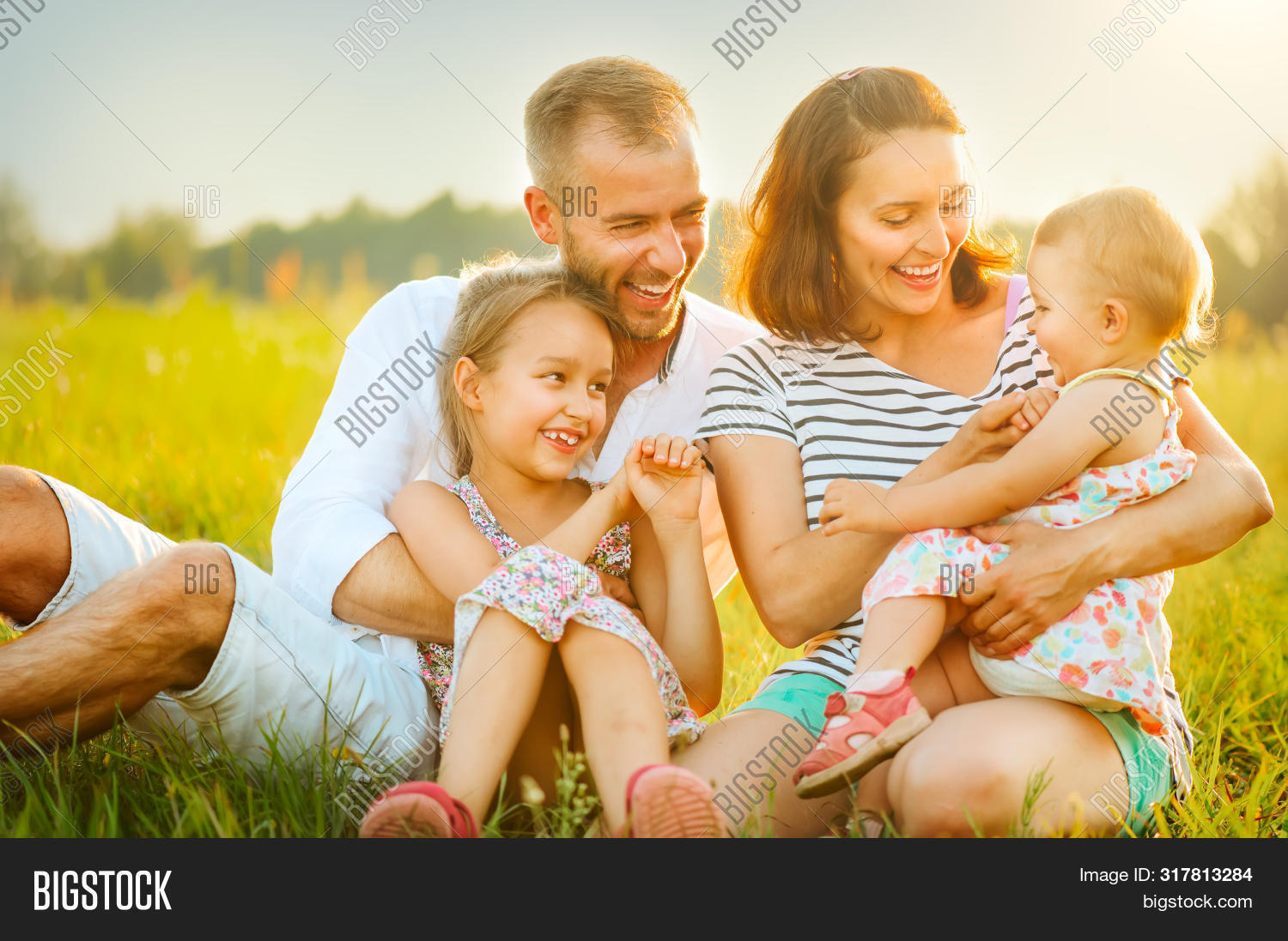 Happy joyful young family father, mother and little daughters having fun outdoors, playing together on a field. Mom, Dad and kids laughing and hugging, enjoying nature outside. Countryside