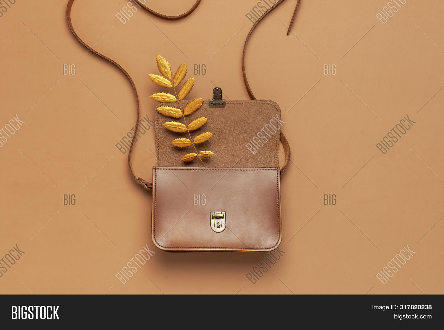 Brown leather women bag and golden autumn leaf on brown background top view flat lay copy space. Fashionable women's accessories. Autumn Fashion Concept. Stylish Lady Clothes, fall Leaves.