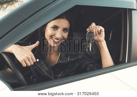 Beautiful car driver woman smiling showing new car keys and car. Caucasian girl sitting in automobile, smiling and demonstrating keys. Female owner of vehicle. Woman is happy to purchase auto stock photo