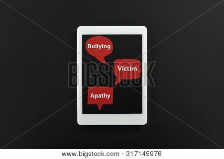 top view of digital tablet and red speech bubbles with bullying, victim and apathy words on black background, cyberbullying concept stock photo