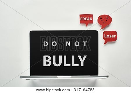 laptop with do not bully lettering on screen on white background near red speech bubbles with offensive words, cyberbullying concept stock photo