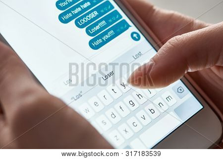 close up view of abuser sending offensive messages while using smartphone, illustrative editorial stock photo
