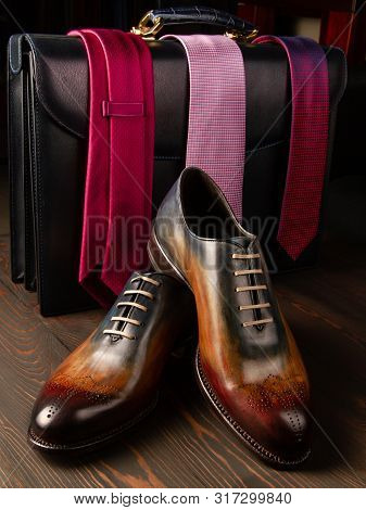 Gorgeous men's shoes on the background of accessories. Men's briefcase in black. Three bright men's ties to choose from. Boss style stock photo